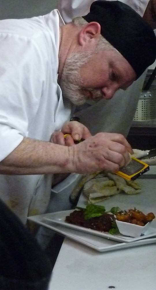 Kenny DeFazio, owner of Sapore Vero in Walpole MA puts the finishing touches on a dish