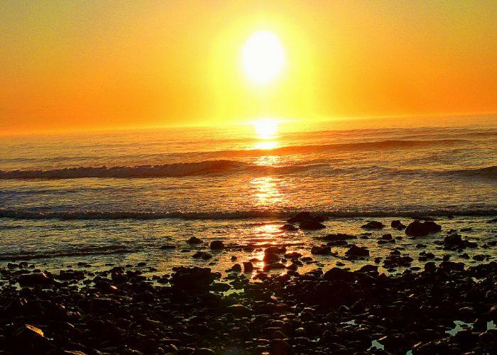 The sun rises at Long Sands Beach in York Beach, Maine.